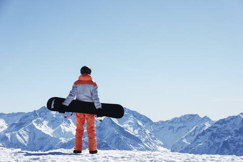 Teenage boy snowboarder looking out over landscape from snow covered mountain top, rear view, Alpe-d'Huez, Rhone-Alpes, France - CUF52820