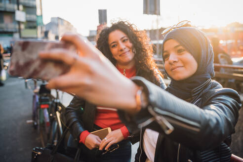 Young woman in hijab with friend taking smartphone selfie in city - CUF52823
