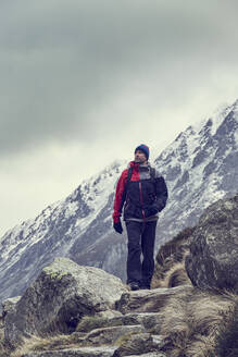Male hiker hiking in rugged landscape with snow capped mountains, Llanberis, Gwynedd, Wales - CUF52862