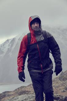 Male hiker looking up while hiking in snow capped mountains with storm clouds, Llanberis, Gwynedd, Wales - CUF52865