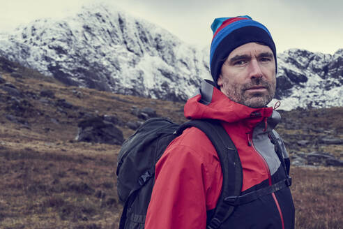 Male hiker in knit hat by snow capped mountains, portrait, Llanberis, Gwynedd, Wales - CUF52883