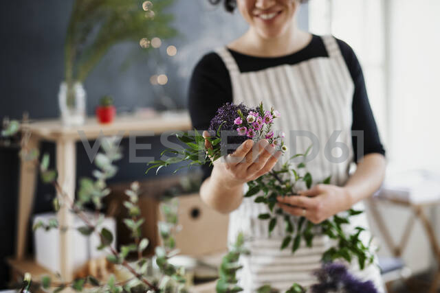 Close-up of woman holding flowers in a small shop - HAPF03027 - HalfPoint/Westend61