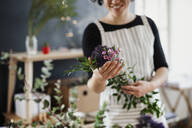 Close-up of woman holding flowers in a small shop - HAPF03027