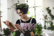 Smiling young woman with clipboard in a small shop with plants - HAPF03030