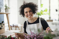 Portrait of happy young woman with clipboard in a small shop with plants - HAPF03033