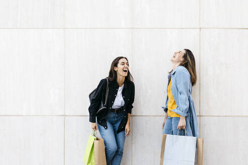 Two friends laughing during shopping - JRFF03793