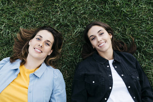 Portrait of two friends looking at camera, lying on the grass - JRFF03808