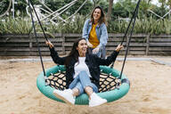 Two friends on playground, woman on a swing - JRFF03811