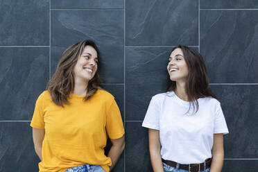 Two friends leaning on a gray wall and laughing - JRFF03817
