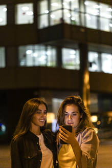 Two friends using the smartphone at night, with city lights in the background - JRFF03820