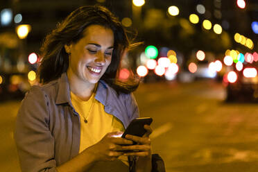 Young woman using smartphone in the city at night - JRFF03823