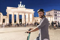Young man with an electric scooter at Brandenburg Gate at night, Berlin, Germany - WPEF02142
