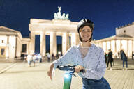 Young woman with an electric scooter at Brandenburg Gate at night, Berlin, Germany - WPEF02145