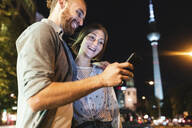 happy couple using smartphones in the city at night, Fernsehturm in the background, Berlin, Germany - WPEF02148