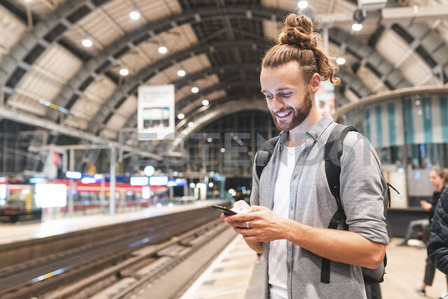 Young smiling man using smartphone on train station - WPEF02157 - William Perugini/Westend61
