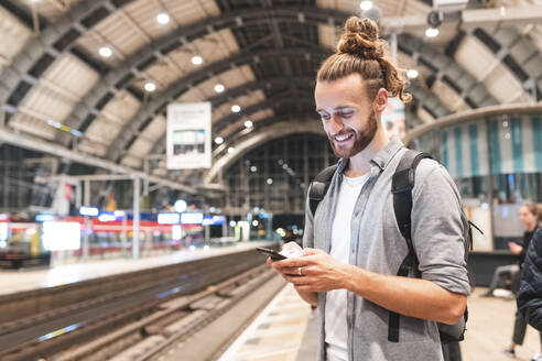 Young smiling man using smartphone on train station - WPEF02157
