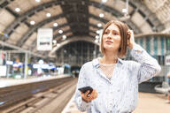 Young unhappy woman using smartphone on train station - WPEF02160