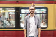 Young man at train station with blurred train as background - WPEF02163