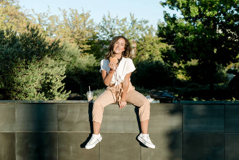 Young woman sitting on wall with hamburger and milkshake, looking at camera - KIJF02678