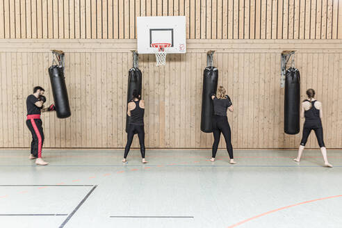 Coach and female boxers practising at punchbags in sports hall - STBF00462