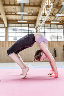 Girl exercising in sports hall - STBF00477
