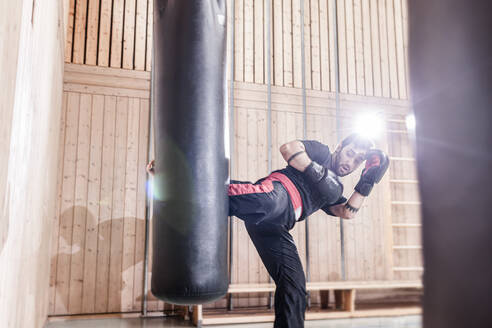Kickboxer practising at punchbag in sports hall - STBF00495