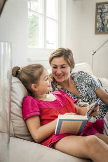 Happy mother and daughter with book on couch in living room - EGBF00370