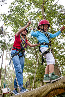 Mother and daughter on a high rope course in forest - EGBF00409