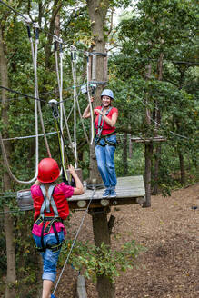 Mother and daughter on a high rope course in forest - EGBF00421