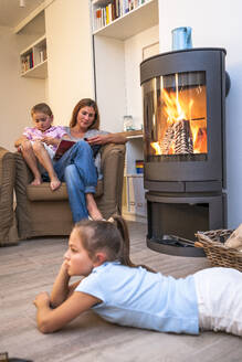 Mother with daughters relaxing and reading in living room at the fireplace - EGBF00439