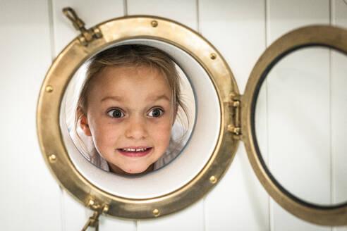 Portrait of grimacing girl looking through porthole - EGBF00454