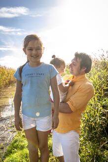 Portrait of a smiling girl with her family at a water course, Darss, Mecklenburg-Western Pomerania, Germany - EGBF00469
