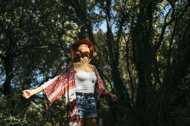 Young woman wearing a brown hat, colorful shirt and white top with closed eyes and arms up feeling the sun in a forest - MTBF00049