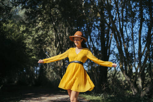 Happy young curly haired woman wearing brown hat and yellow dress walking with open arms and closed eyes with a dark forest in background - MTBF00052