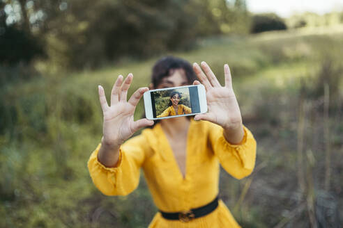 Happy young curly haired and blue eyes woman wearing yellow dress taking a white smartphone in front of her face and taking a photo with forest in background - MTBF00055