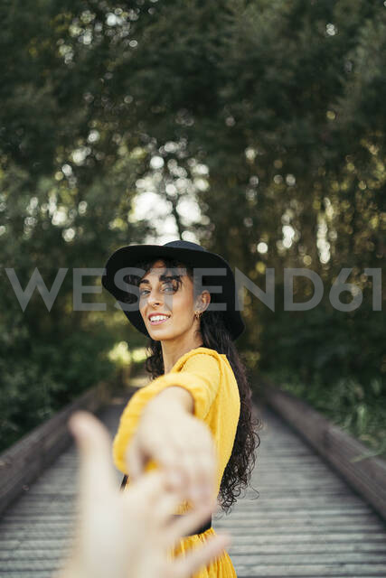 Young woman wearing a black hat and yellow dress and holding a hand - MTBF00058 - Mikel Taboada/Westend61