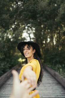 Young curly haired and blue eyes woman wearing a black hat, yellow dress and analog camera holding a hand in a wood bridge with forest bokeh effect in background. Vitoria, Spain - MTBF00058