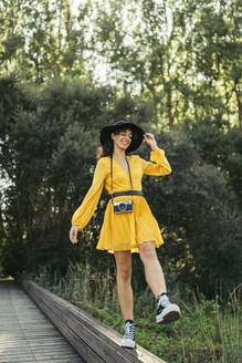 Happy young curly haired and blue eyes woman photographer wearing black hat, yellow dress, black sneakers and analog camera walking along wood bridge with forest in background - MTBF00061