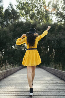 Back view of a young curly haired woman wearing black hat and yellow dress enjoying while is walking along wood bridge with forest in background - MTBF00064