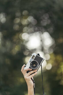 Hand holding grey and black analog camera with forest bokeh effect in background - MTBF00067