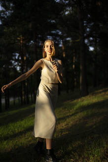 Woman in the forest smiles in motion - CAVF66034
