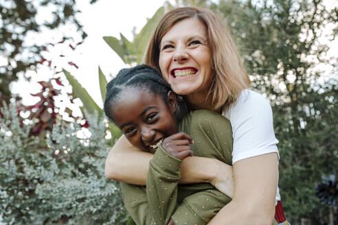 Joyful white mom hugs laughing black daughter - CAVF66406