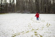 Rear view of boy holding stick while walking on snowy field - CAVF66466