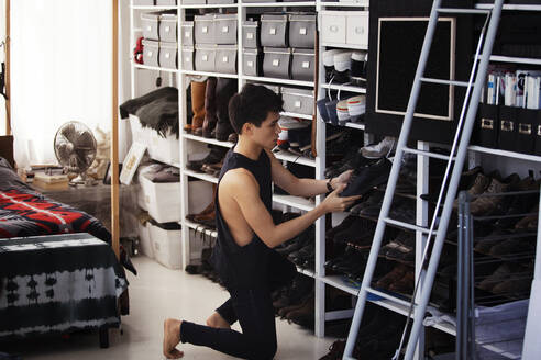 Man removing shoes from shelf in bedroom - CAVF66643