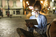Portrait of happy young woman using digital tablet in the city by night, Lisbon, Portugal - UUF19129