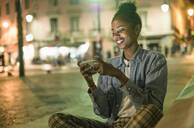 Portrait of happy young woman using smartphone in the city by night, Lisbon, Portugal - UUF19144