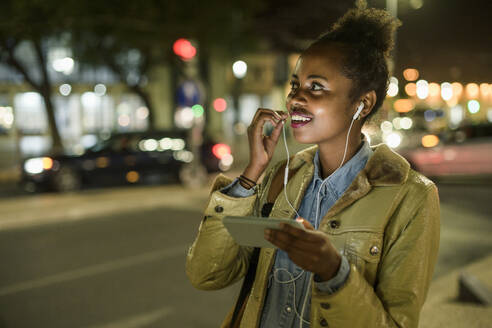 Portrait of smiling young woman using earphones and smartphone in the city by night, Lisbon, Portugal - UUF19156