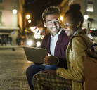 Portrait of smiling young couple using digital tablet in the city by night, Lisbon, Portugal - UUF19162