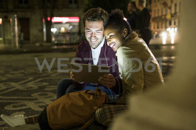 Portrait of happy young couple sharing earphones while looking at digital tablet, Lisbon, Portugal - UUF19165 - Uwe Umstätter/Westend61