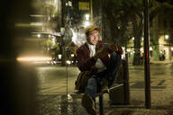 Portrait of young man sitting at bus stop by night using smartphone, Lisbon, Portugal - UUF19174
